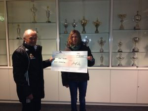 Leder av arrangement komiteen Børge Oanes overrekker det synlige bevis på at Elin Friestad er vinner av årets hovedgevinst i scoringsklubben